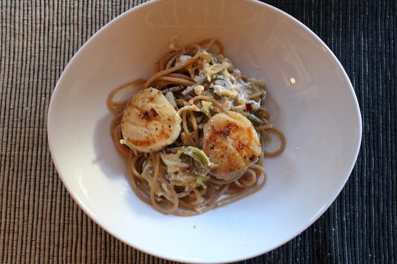 spicy scallops on pasta with fiddlehead ferns